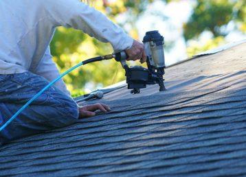 handyman using nail gun to install shingle to repair roof